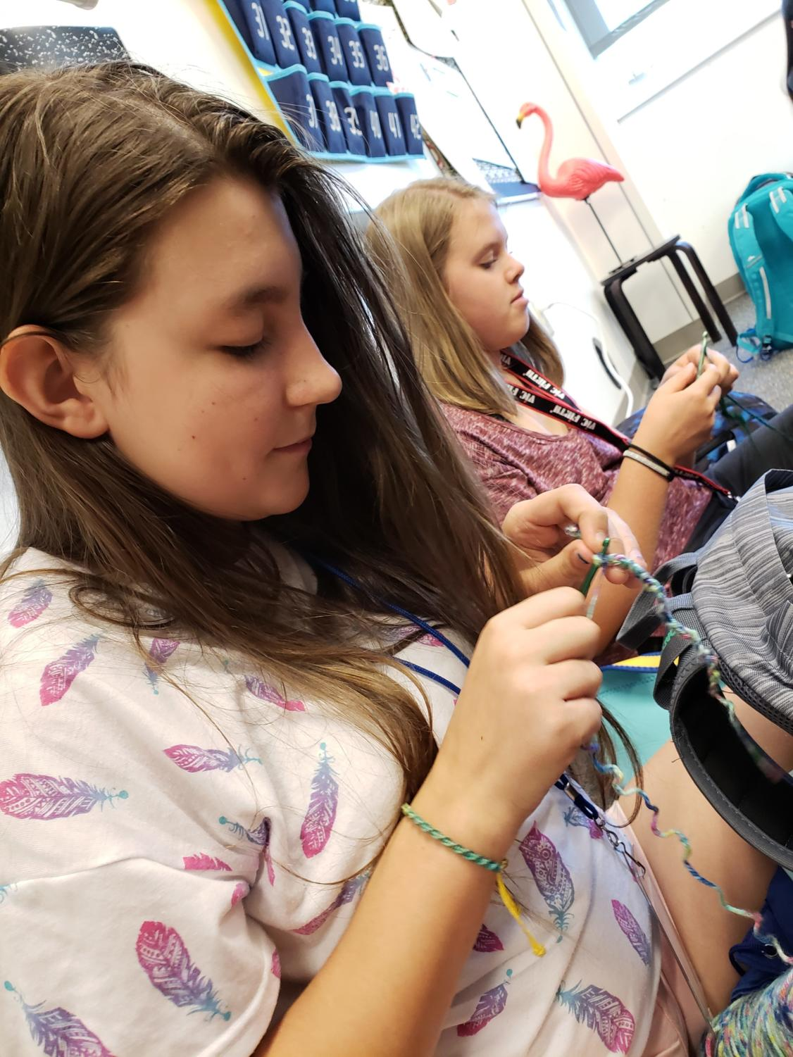 Caption: Stella Olsen (10) and Juliana Brady (9) enjoying eating lunch and crocheting in Mrs. Binion's room.