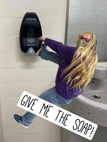 Whatever it Takes:  Kristina hangs desperately from a soap dispenser in the 200 hallway.